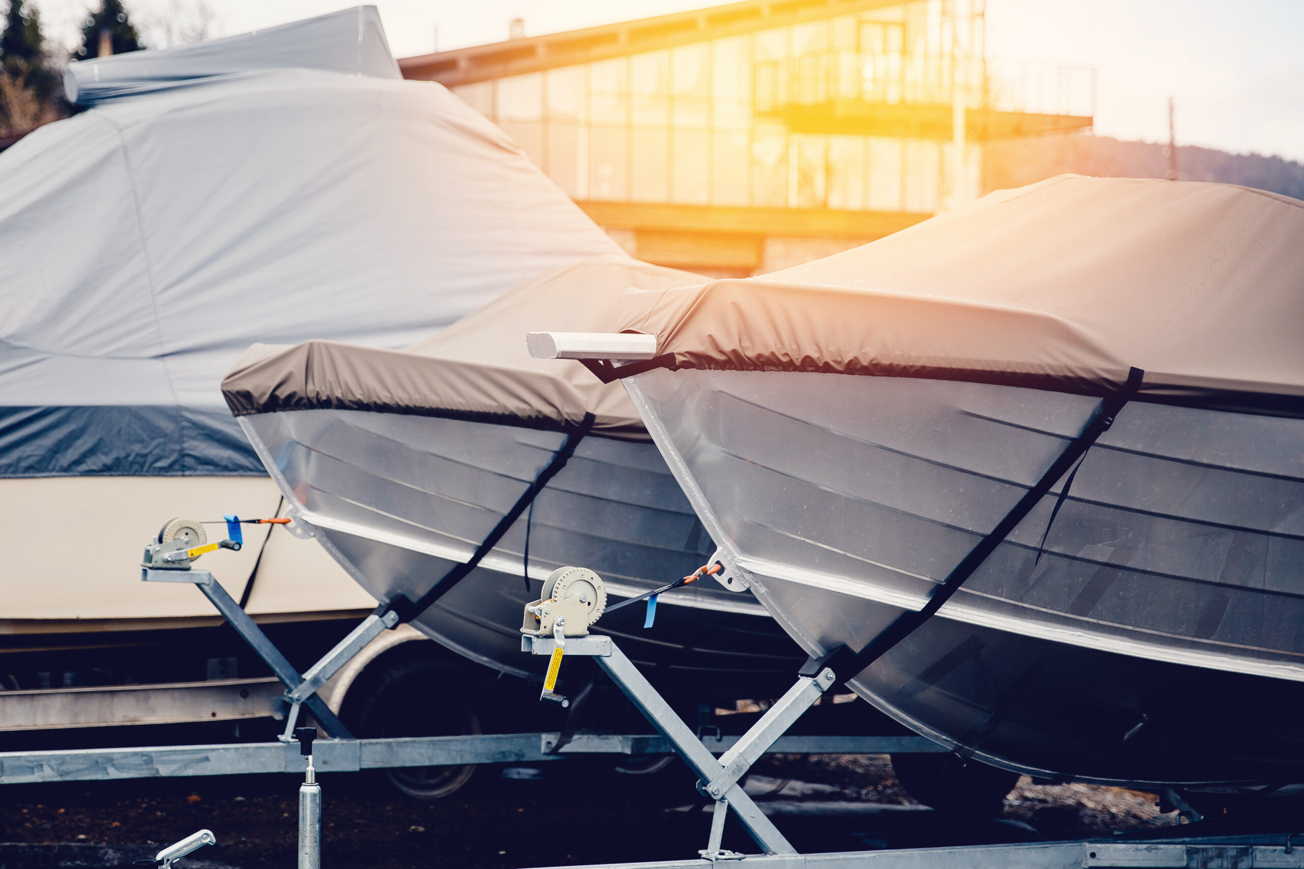 Covered boats in outdoor storage at Leelanau Boat Co